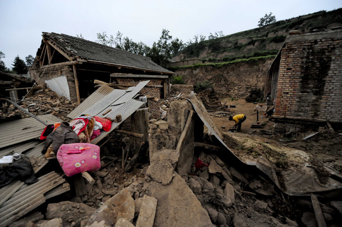 A woman (R) works beside damaged houses in Meichuan township in Dingxi, in northwest China's Gansu province, on July 23, 2013.  Rescuers battled through dusty rubble to try to reach victims of two shallow earthquakes in China that killed at least 92 people, as traumatised survivors struggled with the devastation left behind.    CHINA OUT     AFP PHOTO